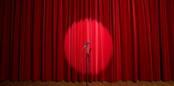 microphone within a spotlight on a wooden stage, befor a closed red stage curtain