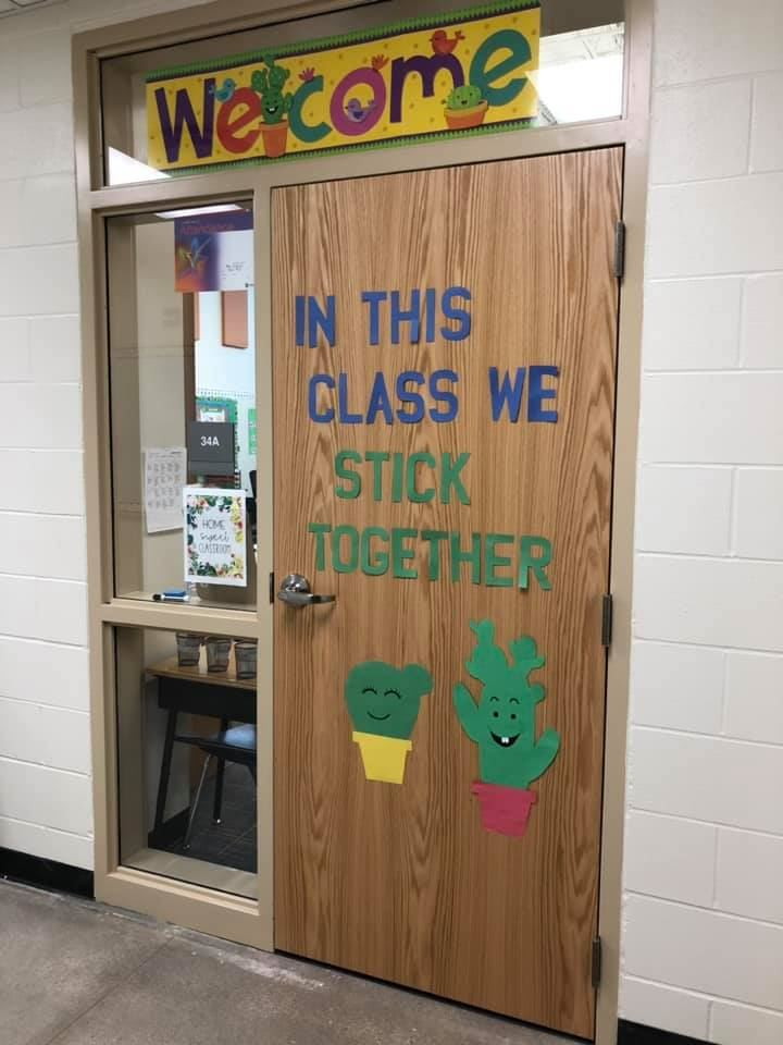 "Classroom door decorated with a Welcome sign and the words ""In this class we stick together"""